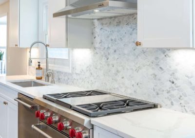 white kitchen with gourmet stove and range