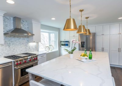 custom colonial white kitchen remodel with gold pendant lights