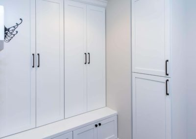 mudroom with white built in storage and coat hooks