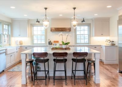 white kitchen with island and hardwood floors
