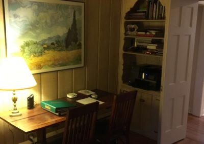 dimly lit library with desk and built-in bookshelf