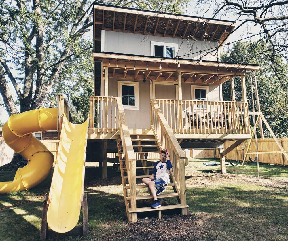 Ian and exterior of his treehouse and playset