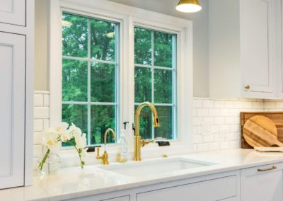 white shaker kitchen cabinets and sink with gold hardware
