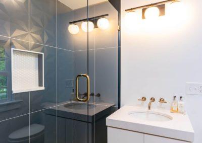 walk in shower with glass door next to wall mounted vanity
