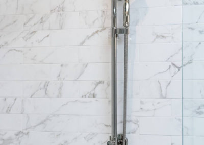 shower head and sprayer in white marble tile shower