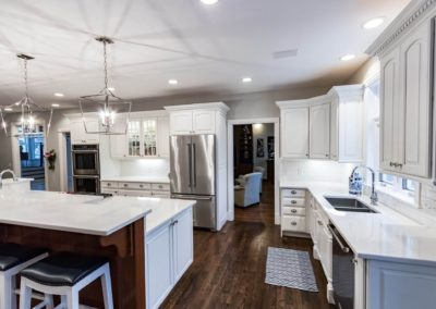 white kitchen with stainless steel appliances and dark wood floors
