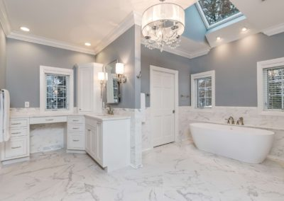 large bathroom with soaker tub and marble floors